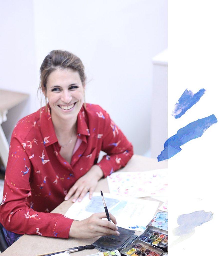 Lou Ripoll, la créatrice de Bleu Tango, marque française de mode éthique et de vêtements eco-responsable. Lou est dans son atelier à Paris en train de dessiner ses motifs à l'aquarelle, elle porte une chemise motif Acrobates.